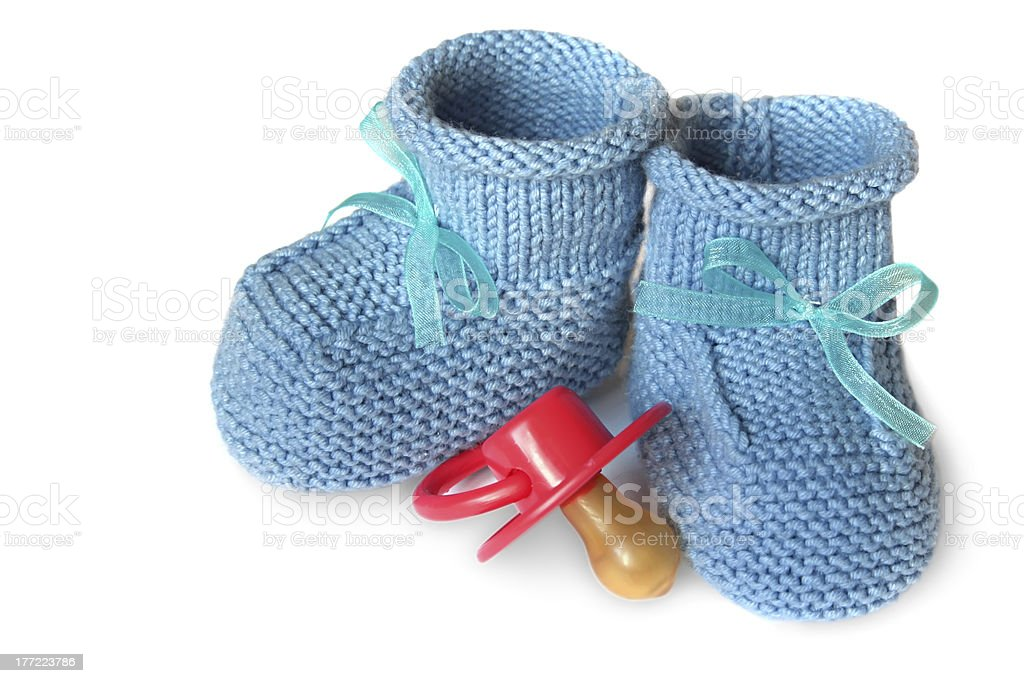 pair of blue knit children's bootees and baby's dummy stock photo