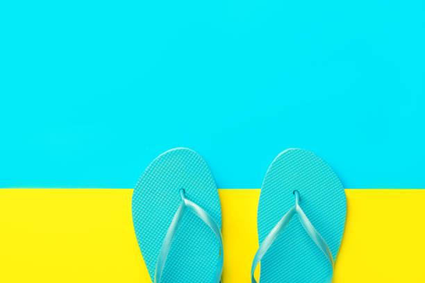 Ein Paar blaue Gummi-Strandschuhe auf duotone leuchtend gelbe Cyan-Hintergrund. Nachahmung von Sand und Meer. Kreative Wohnung. Sommerurlaub Reise Entspannung tropisches Thema – Foto