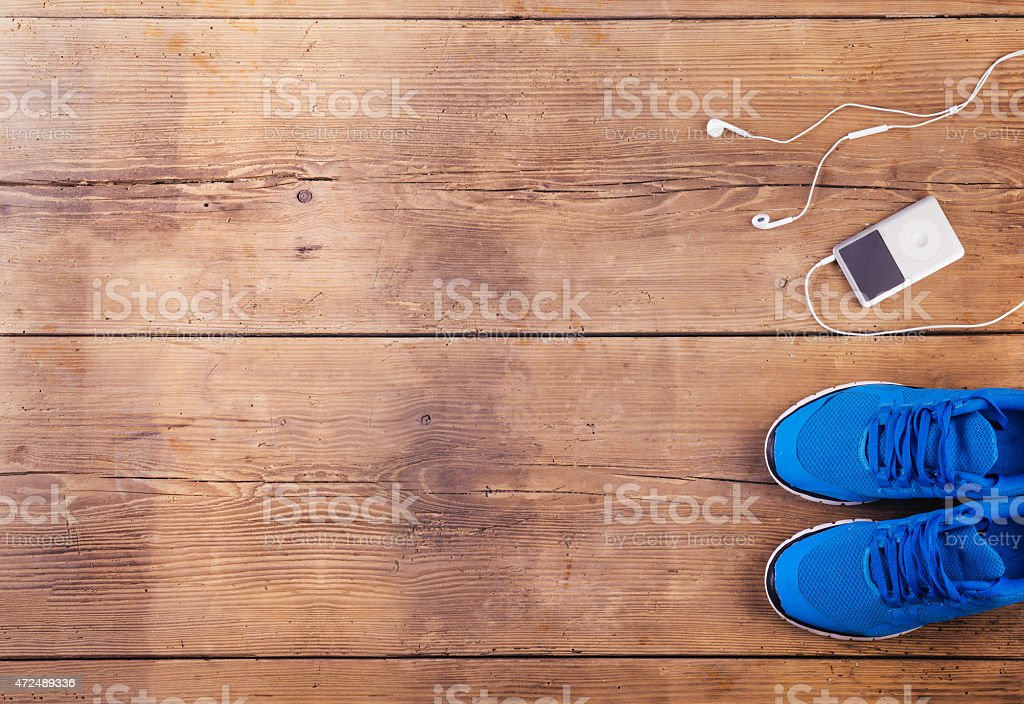 A pair of blue sneakers and a music player on a wooden floor stock photo