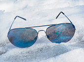 Pair of blue sunglasses in cold icy snow, without a face at winter in sunlight