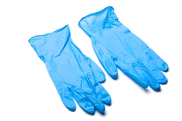 pair of blue surgical gloves laying on white background - latex stock pictures, royalty-free photos & images