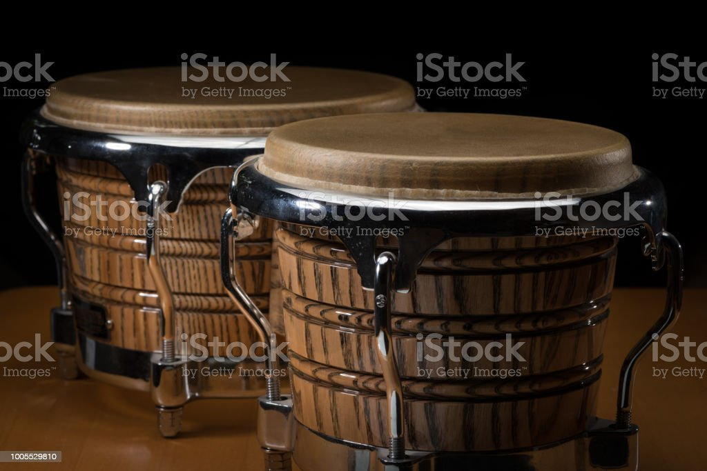 A pair of bongos standing on a wooden table, black background stock photo