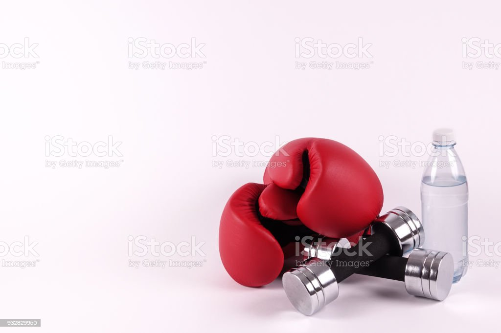 A pair of boxing gloves and dumbbells stock photo