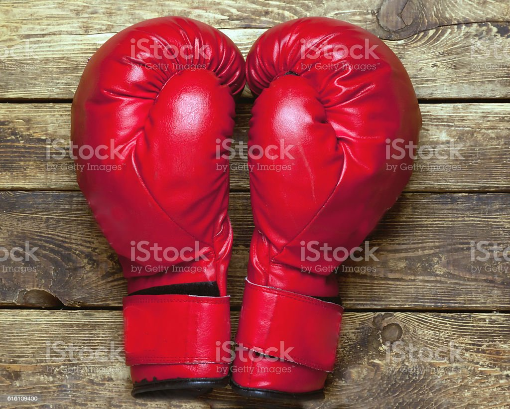pair of boxing gloves on wooden surface stock photo