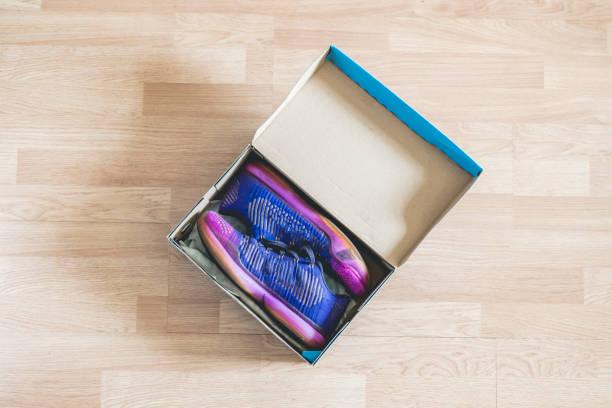 brandneue schuhe in cartoon schuhkarton auf holzboden f - neue sneaker stock-fotos und bilder