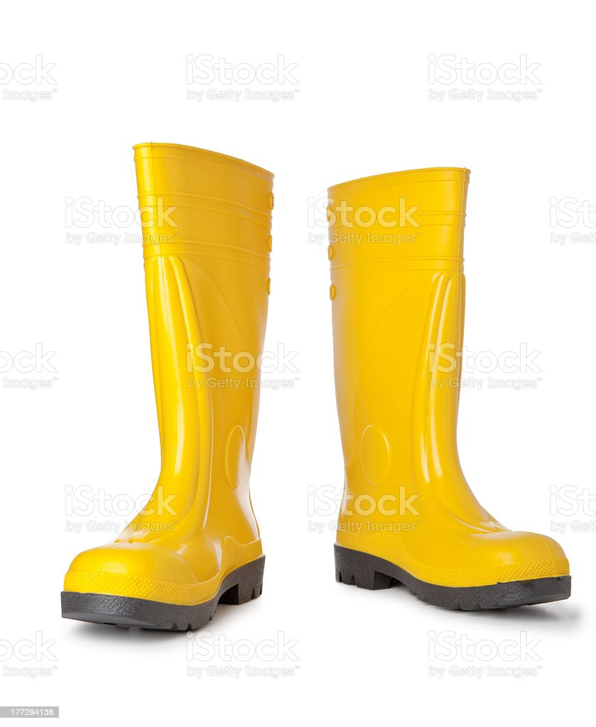 A pair of bright yellow rain boots on white background stock photo