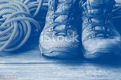 istock A pair of brown worn boots and a sport rope on a wooden background. Selective focus. Concept of travel and adventure. 1192679149