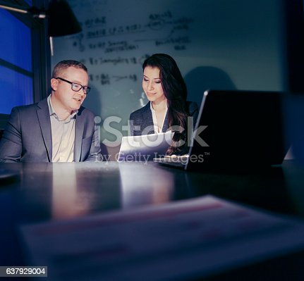 1063657732 istock photo Pair of colleagues reviewing documents in office late at night 637929004