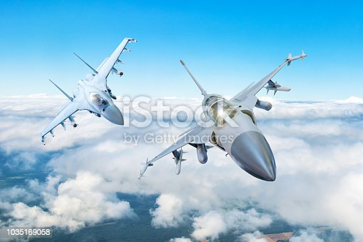 istock Pair of combat fighter jet on a military mission with weapons - rockets, bombs, weapons on wings flies high in the sky above the clouds. 1035169058