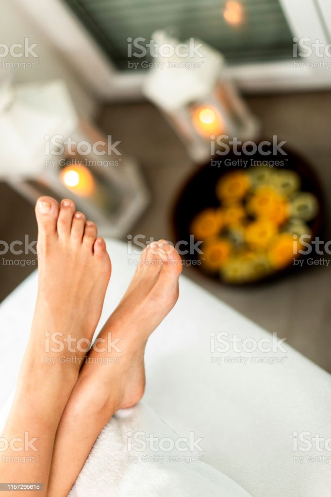 Crossed woman\'s feet above a bowl with water in a spa center.
