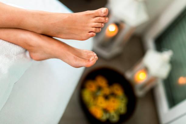 Ein Paar gekreuzte weibliche Füße über einer Schüssel mit Wasser in einem Spa – Foto