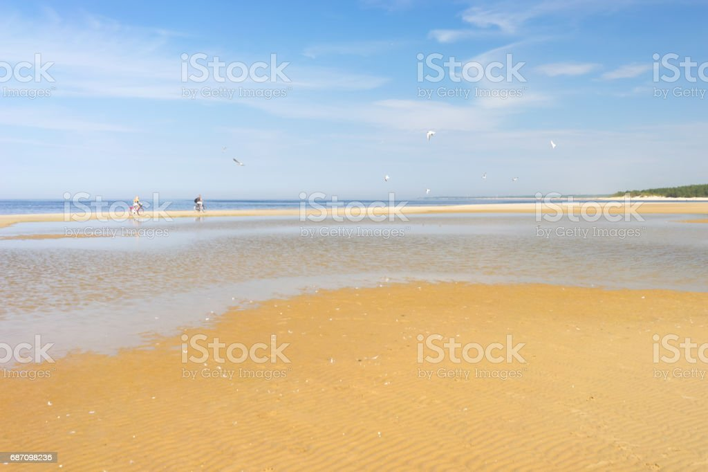 Pair of cyclists on the beach stock photo
