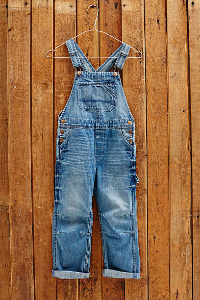 Pair of denim dungarees hanging against wooden wall stock photo