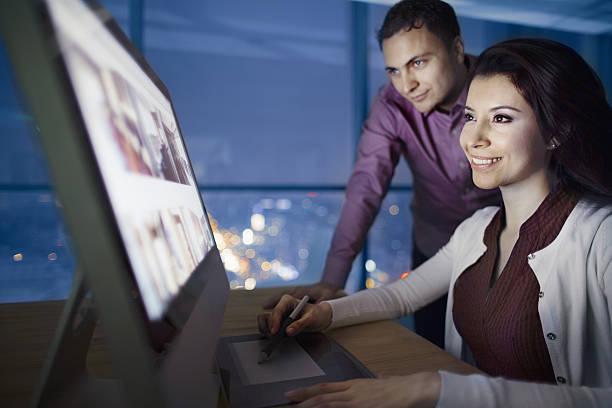 pair of designers reviewing images on computer at night - gute webseiten stock-fotos und bilder