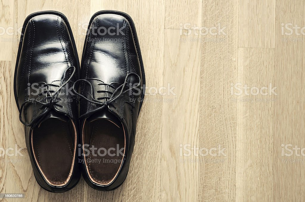 Pair of dress shoes on wooden floor stock photo
