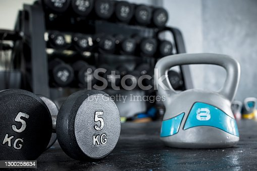 A pair of dumbbells and a kettlebell lying on the floor of a gym. A dumbbell rack visible in the background.
