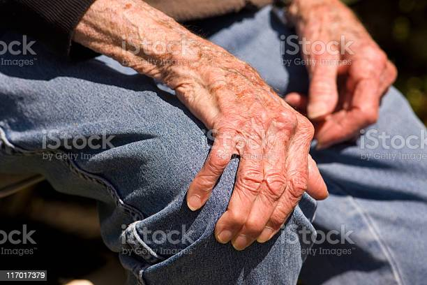 A Pair Of Elderly Hands Grasping A Denim Clad Knee Stock Photo - Download Image Now