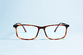 A pair of elegant and classic eyeglasses with thick and vintage frames on a uniform white background