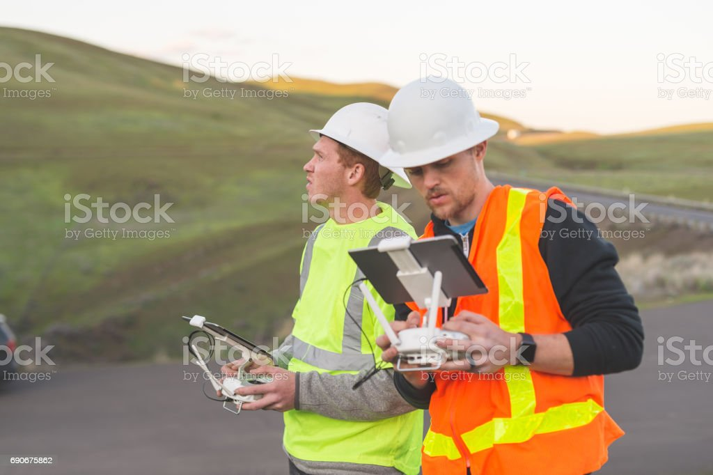 A pair of engineers use a drone to inspect wind farms and power plants in the country stock photo
