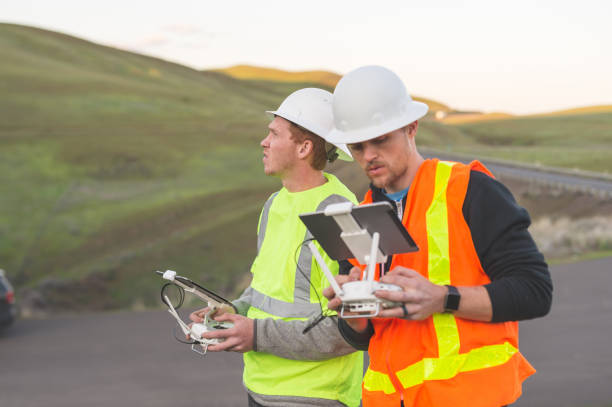 a pair of engineers use a drone to inspect wind farms and power plants in the country - drones stock photos and pictures