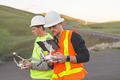 A pair of engineers use a drone to inspect wind farms and power plants in the country