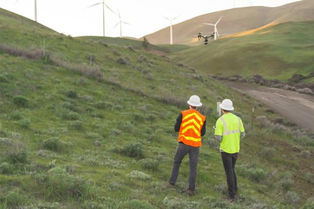 ein paar ingenieure verwenden eine drohne, windparks und kraftwerke im land zu inspizieren - flugdrohne stock-fotos und bilder