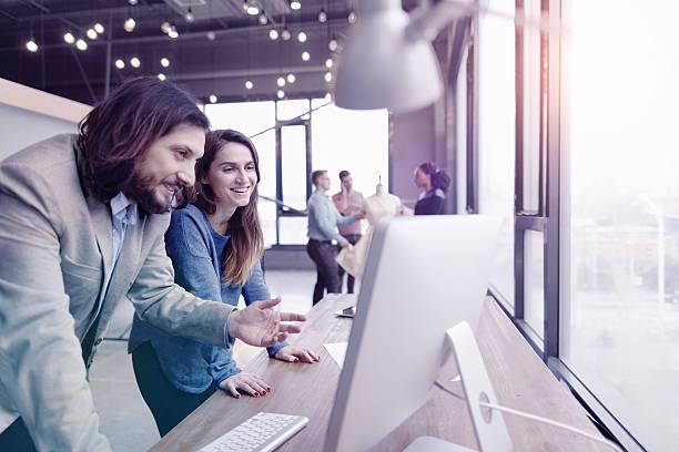 pair of fashion designers discussing ideas in design studio environment - modisch leger frauen stock-fotos und bilder