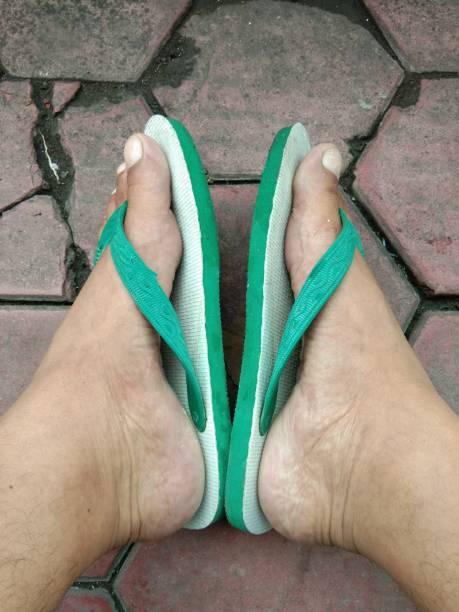 ein paar füße mit grünen gummisandalen - flip flops reparieren stock-fotos und bilder