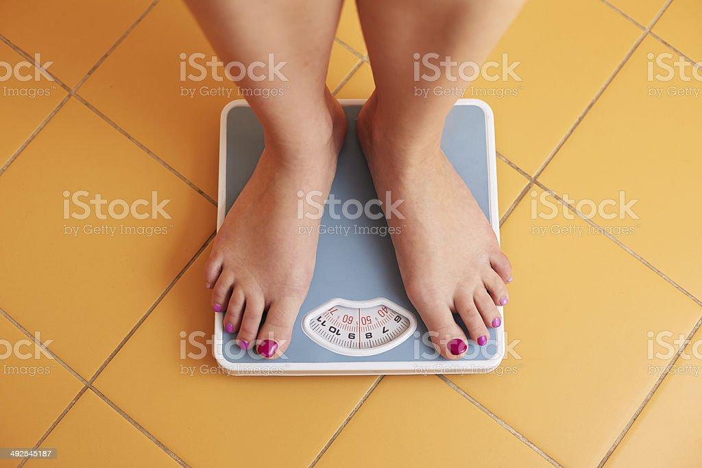 Pair of female feet on a bathroom scale A pair of female feet standing on a bathroom scale Adult Stock Photo