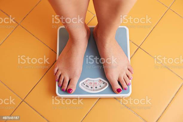 Pair Of Female Feet On A Bathroom Scale Stock Photo - Download Image Now