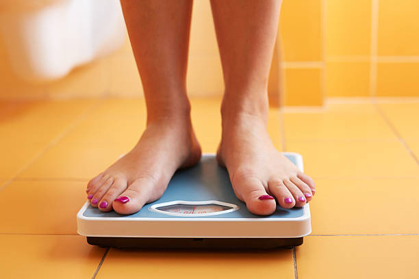 pair of female feet on a bathroom scale - scale stock photos and pictures