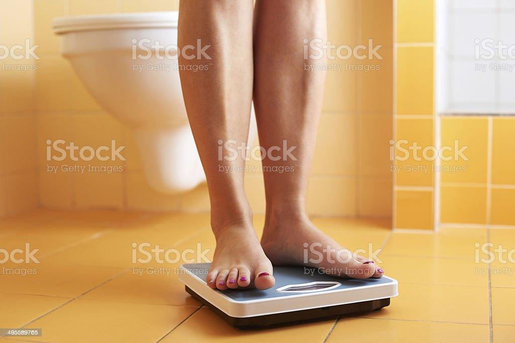 Pair of female feet on a bathroom scale stock photo