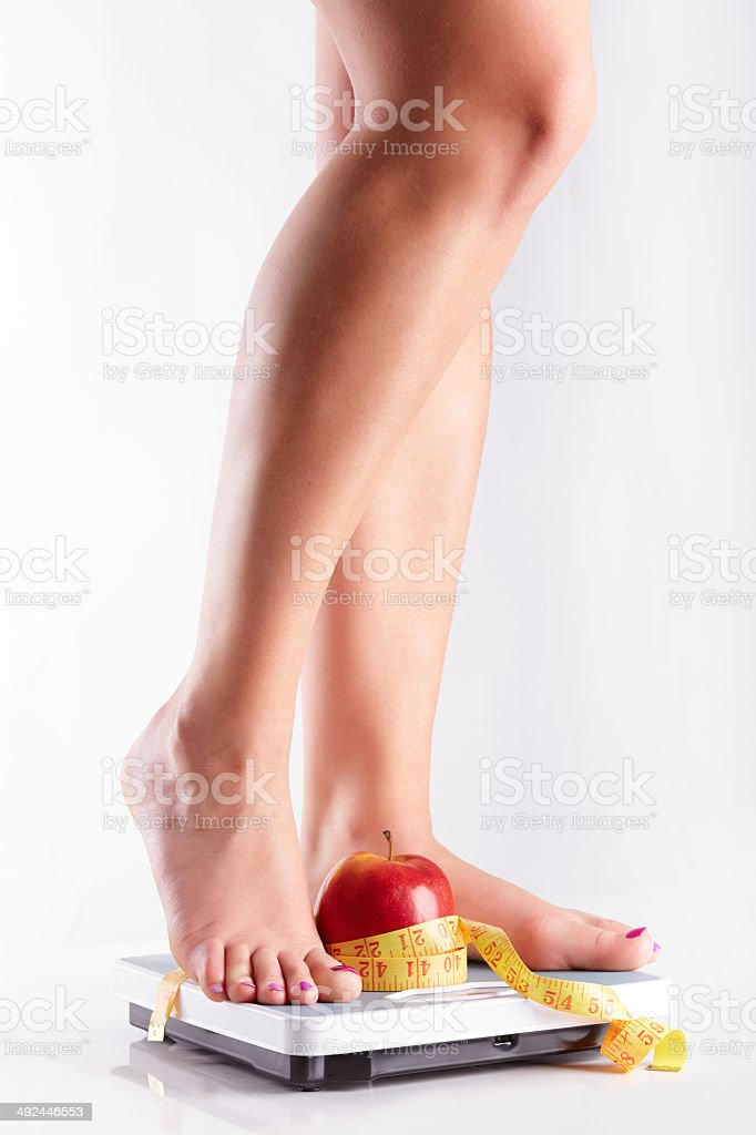 Pair of female feet standing on a bathroom scale stock photo