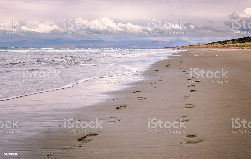 Pair of foot prints on a deserted beach stock photo