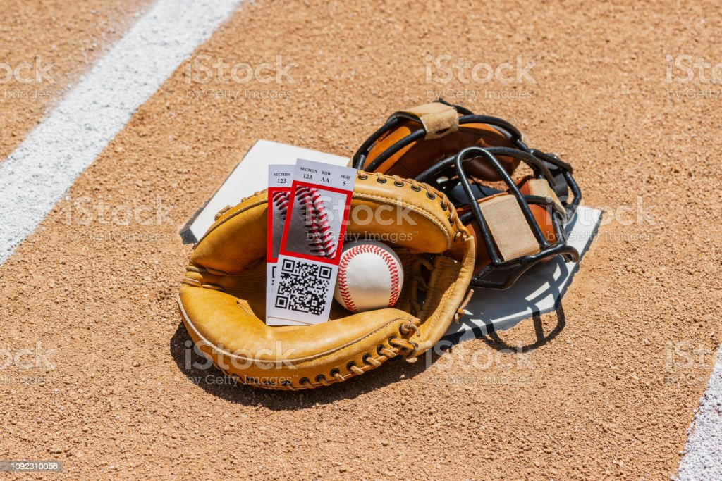 A low angle view of a pair of game ticket stubs with a baseball in a...