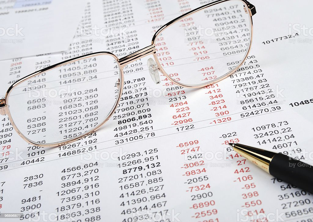 A pair of glasses and pen on top of a financial report royalty-free stock photo