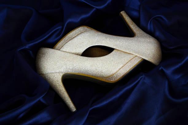 paar gold high heels im feld seide. die luxus-hintergrund. - glitzer absätze stock-fotos und bilder