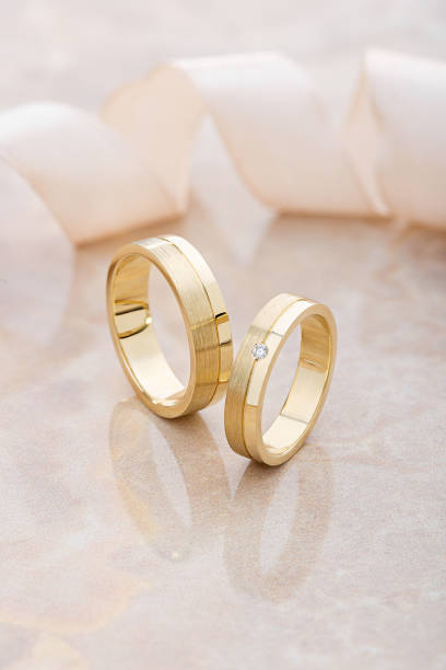 Pair of gold wedding rings on beige background