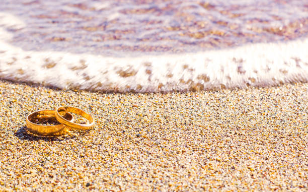 paar gold trauringe auf sand strand meer - hochzeitsreise zypern stock-fotos und bilder