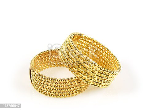 Pair of braided gold rings, brightly lit on white background, perfect for wedding, romance, trust, wealth. Matching style and size ideal for gay marriage concept.