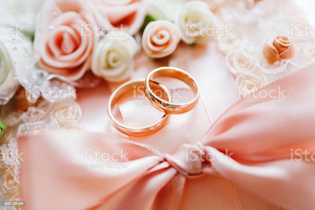 Paar Goldene Hochzeit Ringe auf Spitze Stoff mit Rosen und Bogen. Textile hochzeitsdetails. Symbol für Liebe und Ehe. – Foto