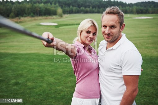 A pair of golfers make a photo on the golf course using a stick like a sephi pole.
