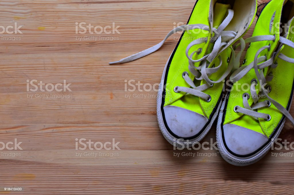 A pair of green sneakers at wooden background stock photo