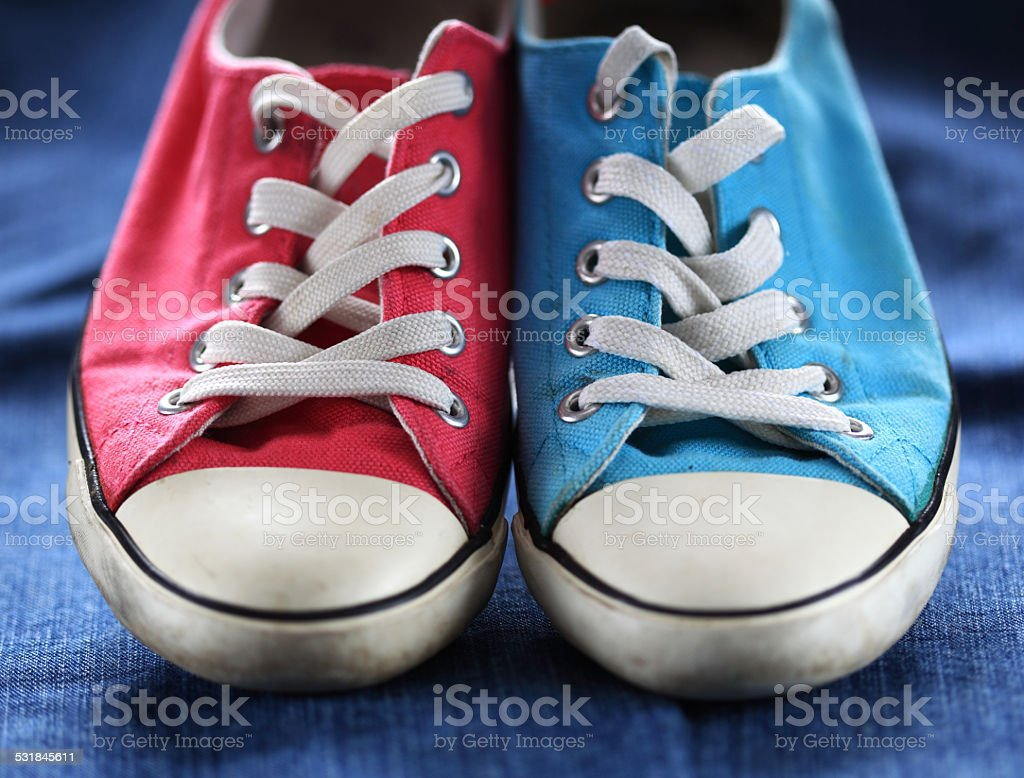 Pair of gym shoe on jeans stock photo
