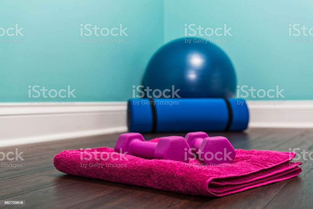 A pair of hand weights on towel with yoga ball and mat at home. stock photo