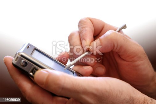 Male hand with digitized pen, touching the screen of a PDA.