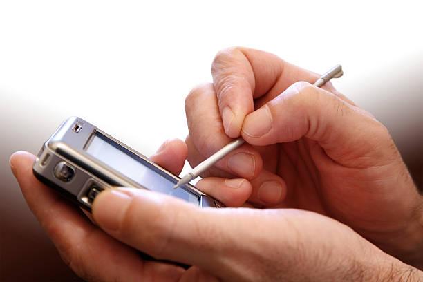 la main avec un assistant numérique personnel - palm photos et images de collection