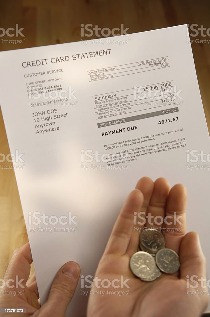 Pair of hands holding credit card statement and coins. royalty-free stock photo