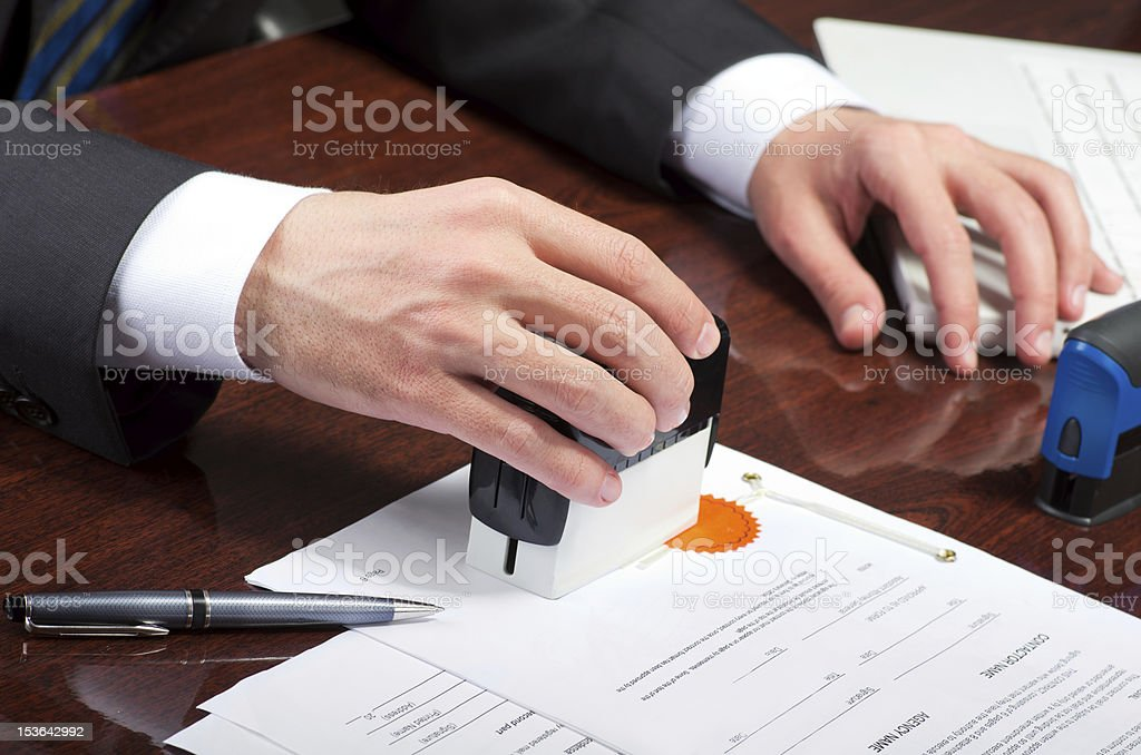 Pair of hands placing stamp on a contract to sign it stock photo