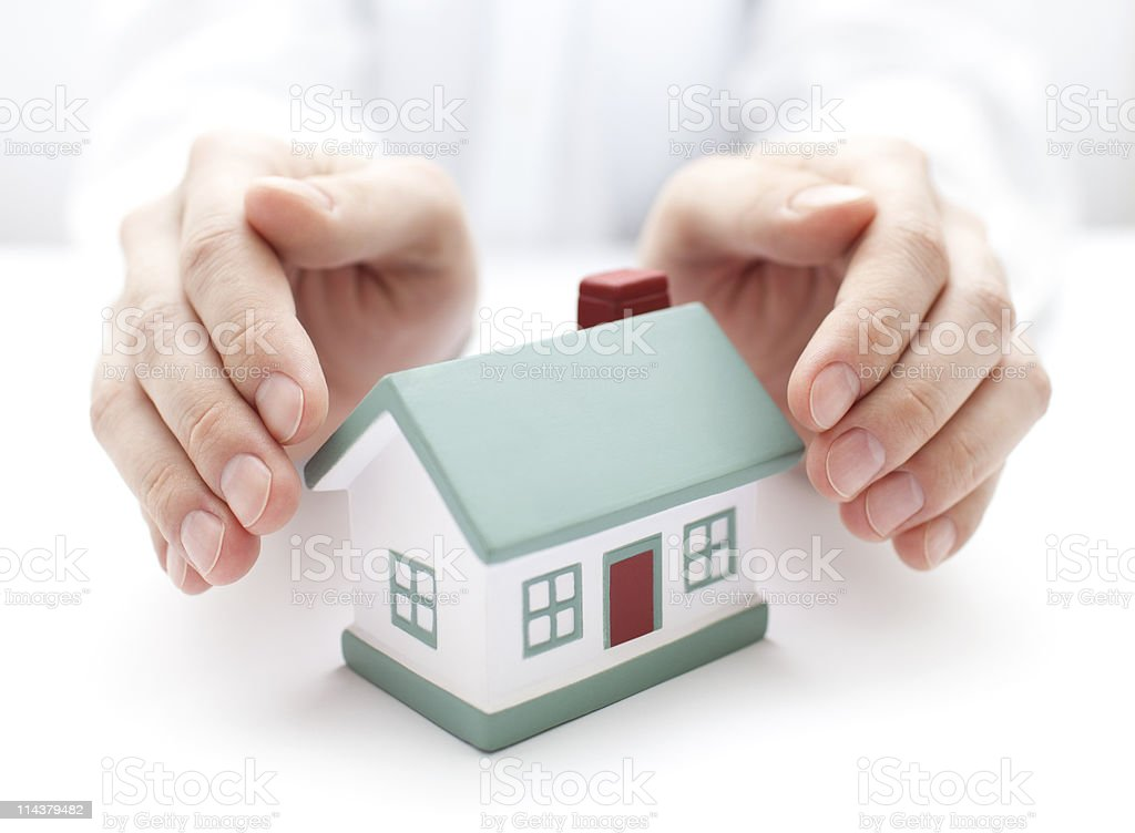 Pair of hands protecting miniature house royalty-free stock photo